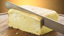 Taleggio cheese on cutting board sliced