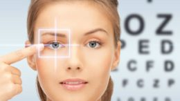 medicine, eyesight control, laser correction, people and health concept - beautiful young woman pointing finger to her eye and over blue background with eye chart